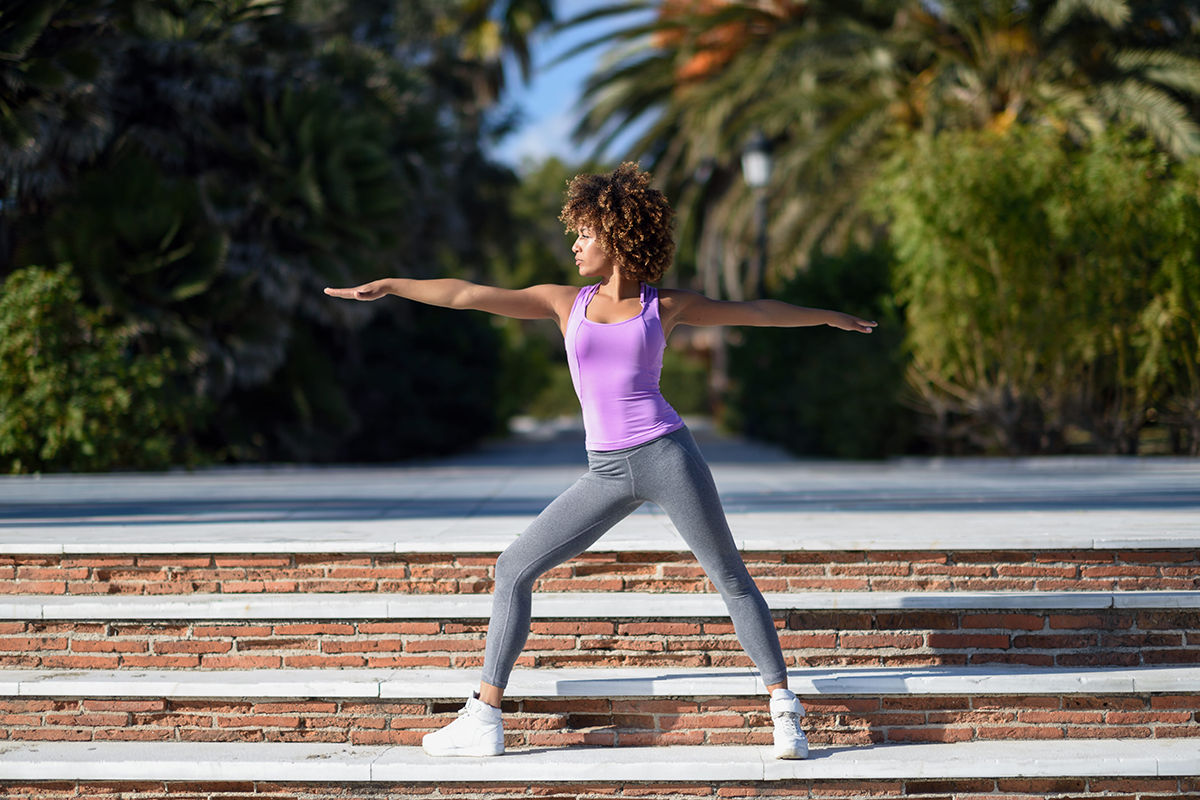 Black woman adopting warrior yoga pose outside on a bright sunny day