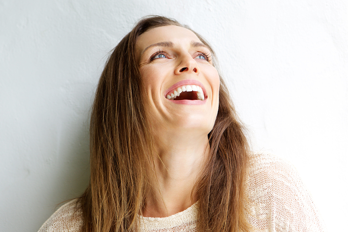 Woman looking up and smiling on a well lit white background