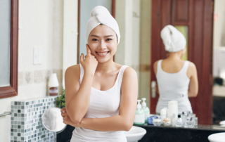 Asian woman in bathroom with white towel wrapped around head, face on hands and smiling