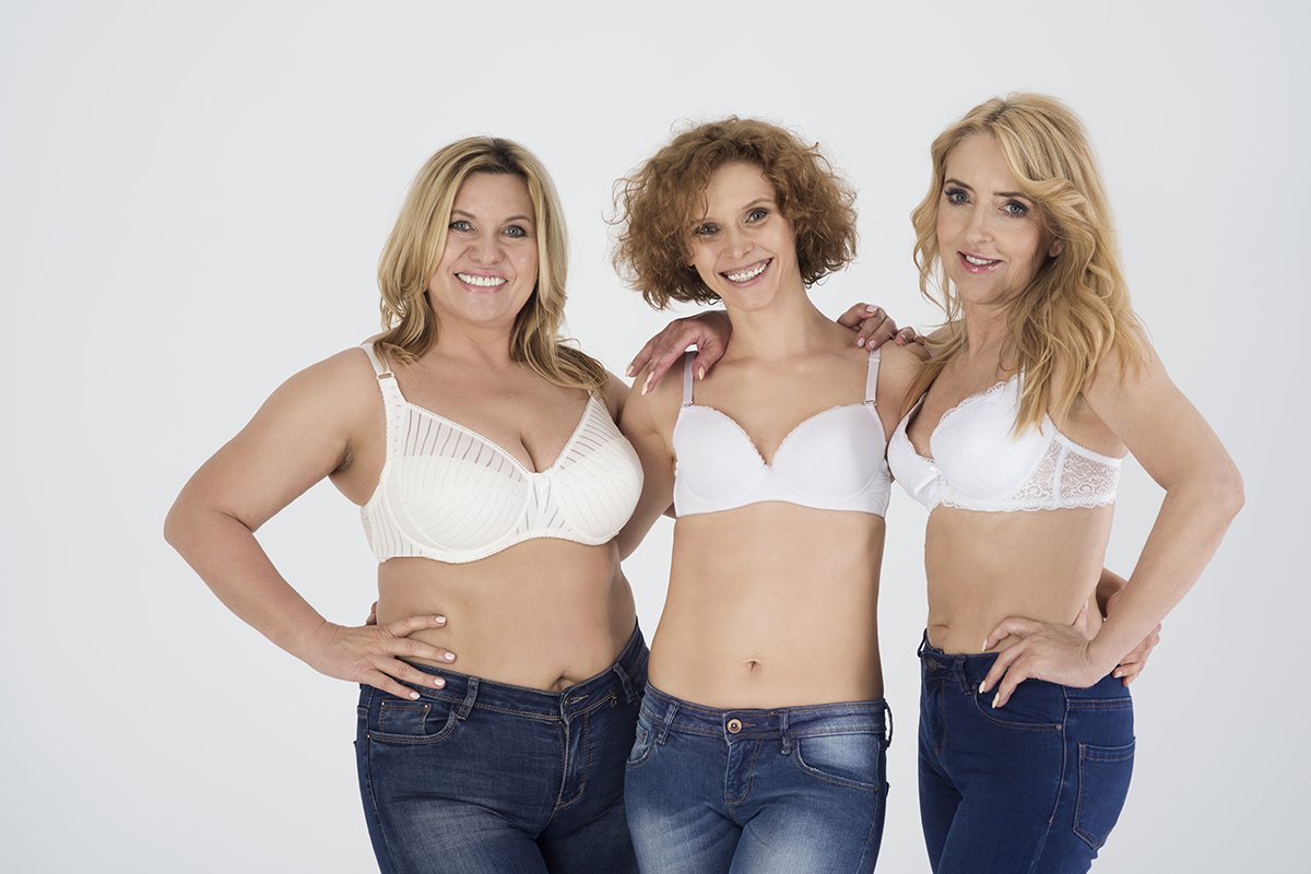 Three confident women in jeans and bras smiling and embracing