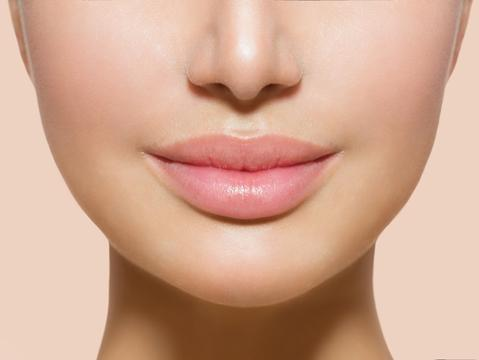 Close up of a womans lips where, the lips are plump and light pink coloured and the skin around the mouth is smooth